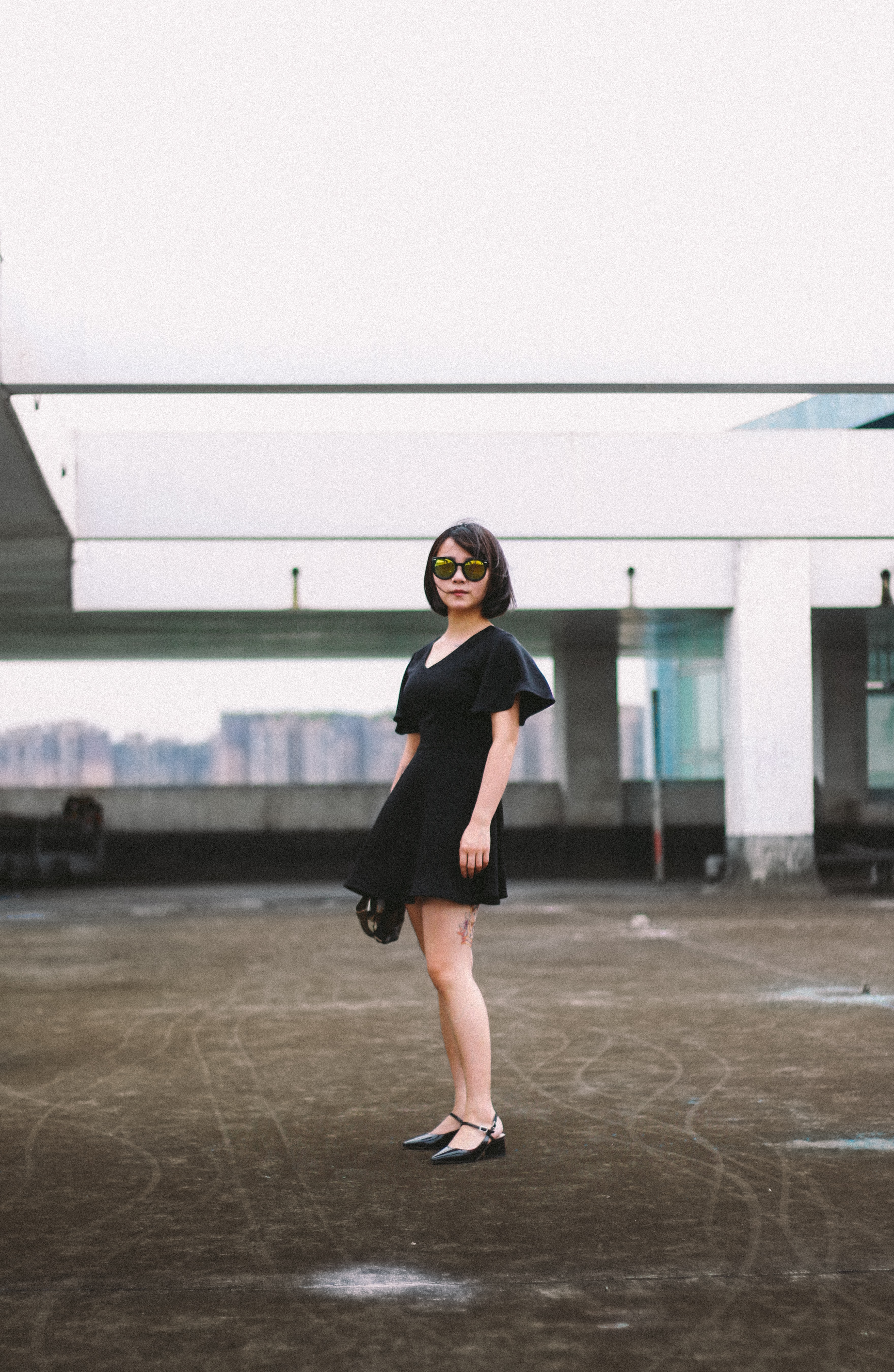woman in black minidress and black sunglasses standing on street