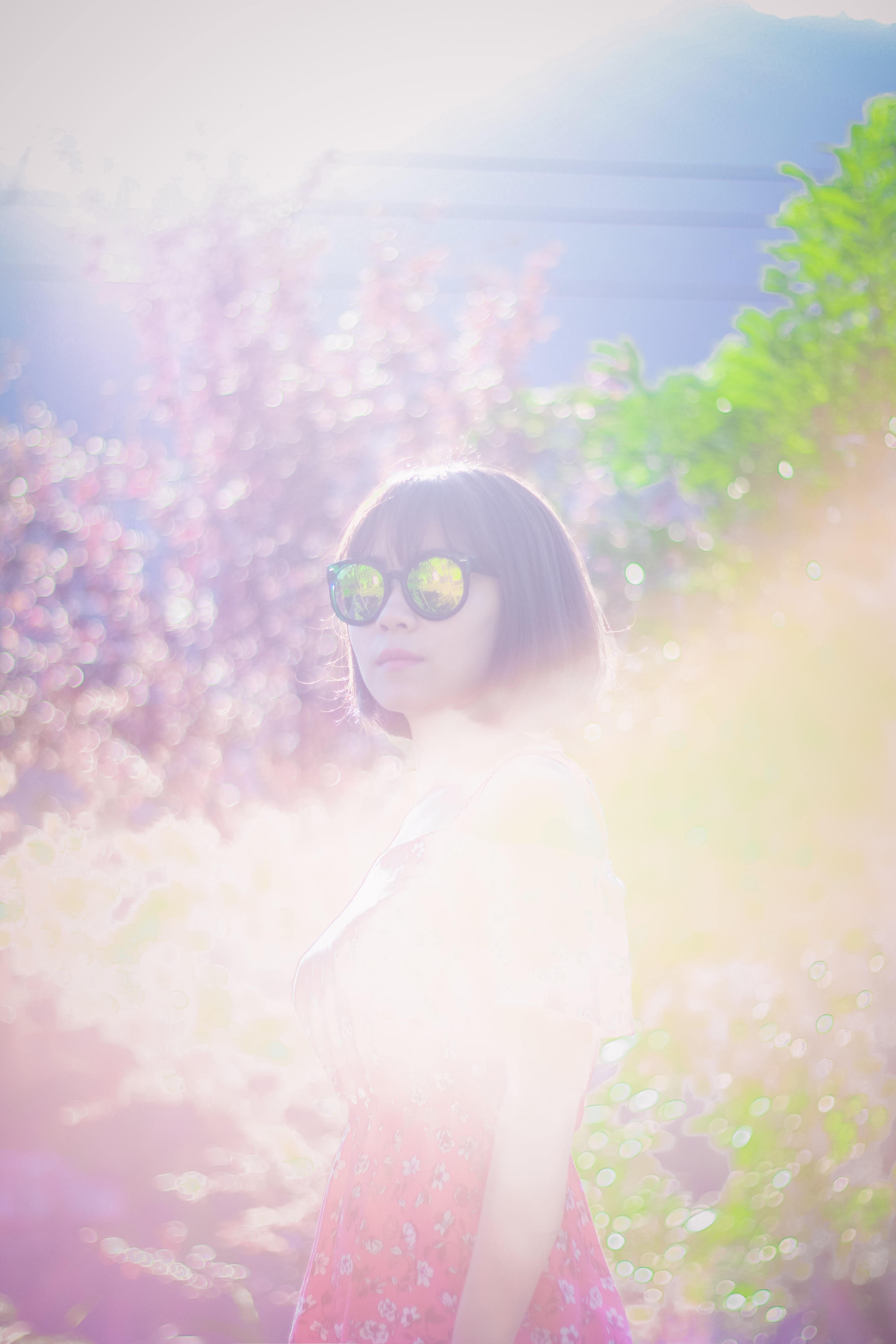 woman wearing sunglasses while standing near trees