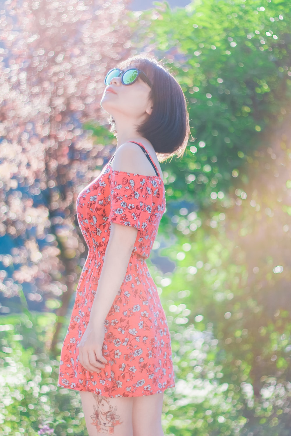 woman wearing dress and sunglasses standing near trees