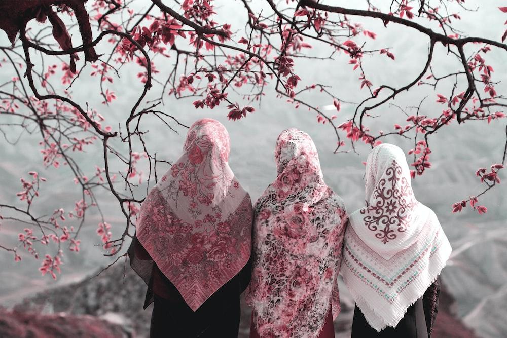 three woman standing near tree