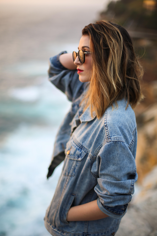 woman in blue denim jacket standing beside cliff