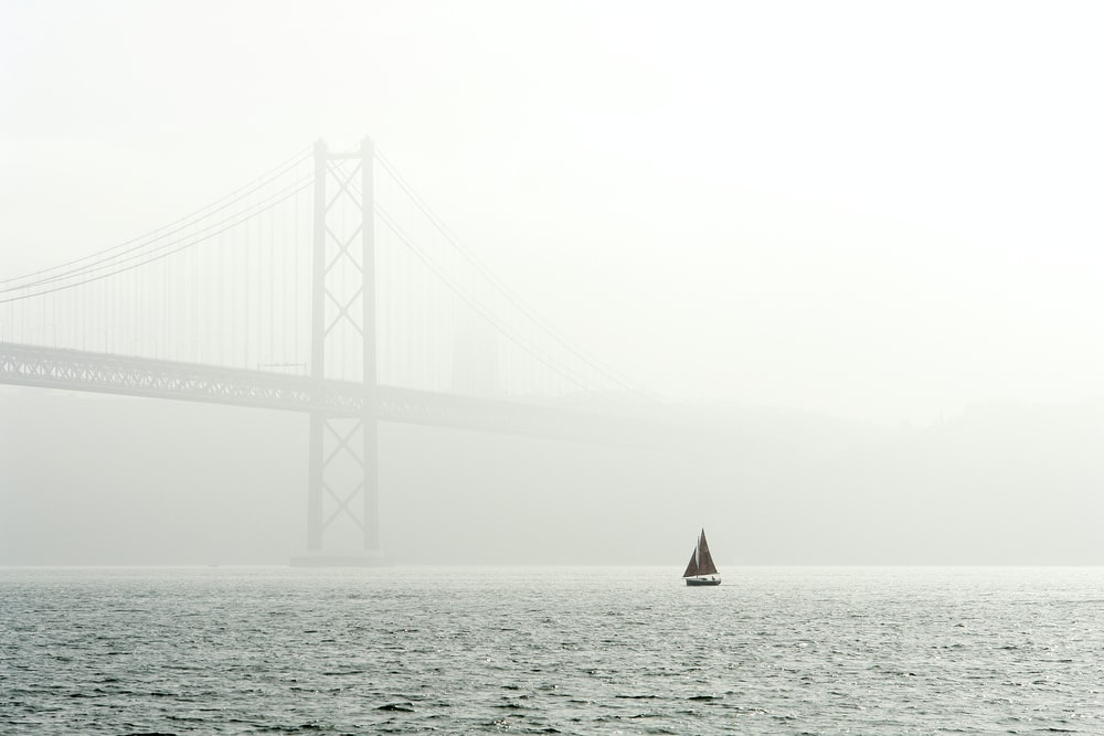 sailing boat on body of water near bridge covered by fog