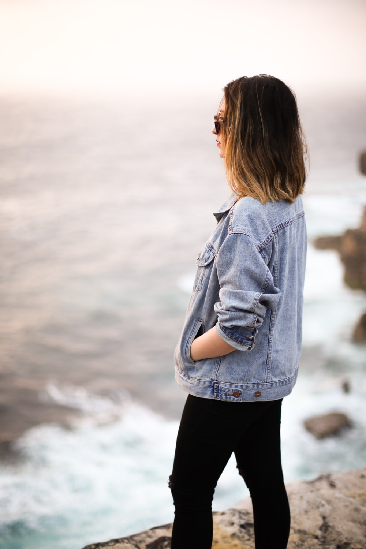 woman wearing blue denim jacket on cliff facing body of water