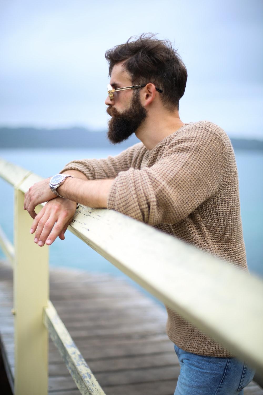 man wearing brown sweater standing on wooden dock