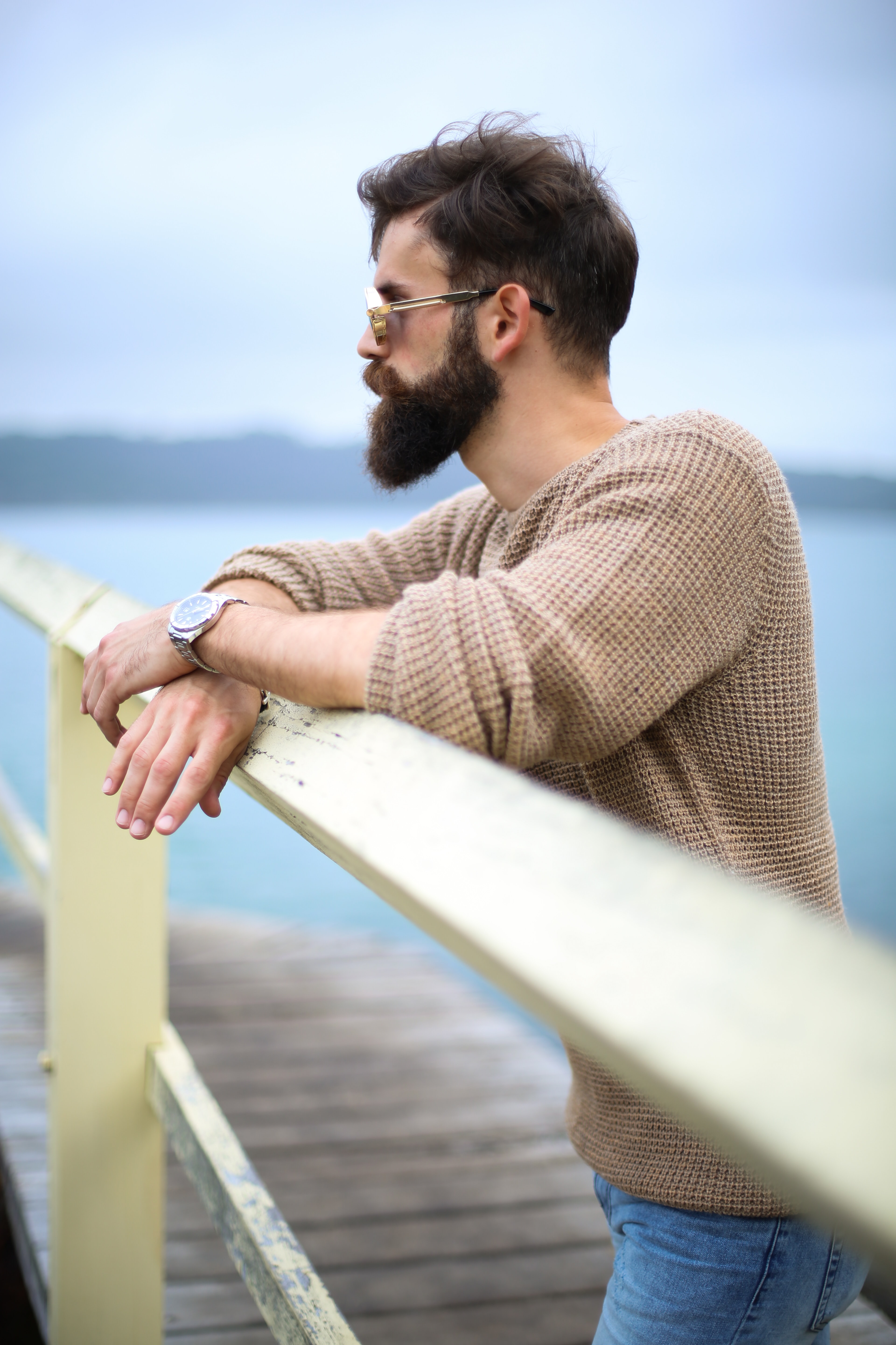 man wearing brown sweater standing on wooden dock