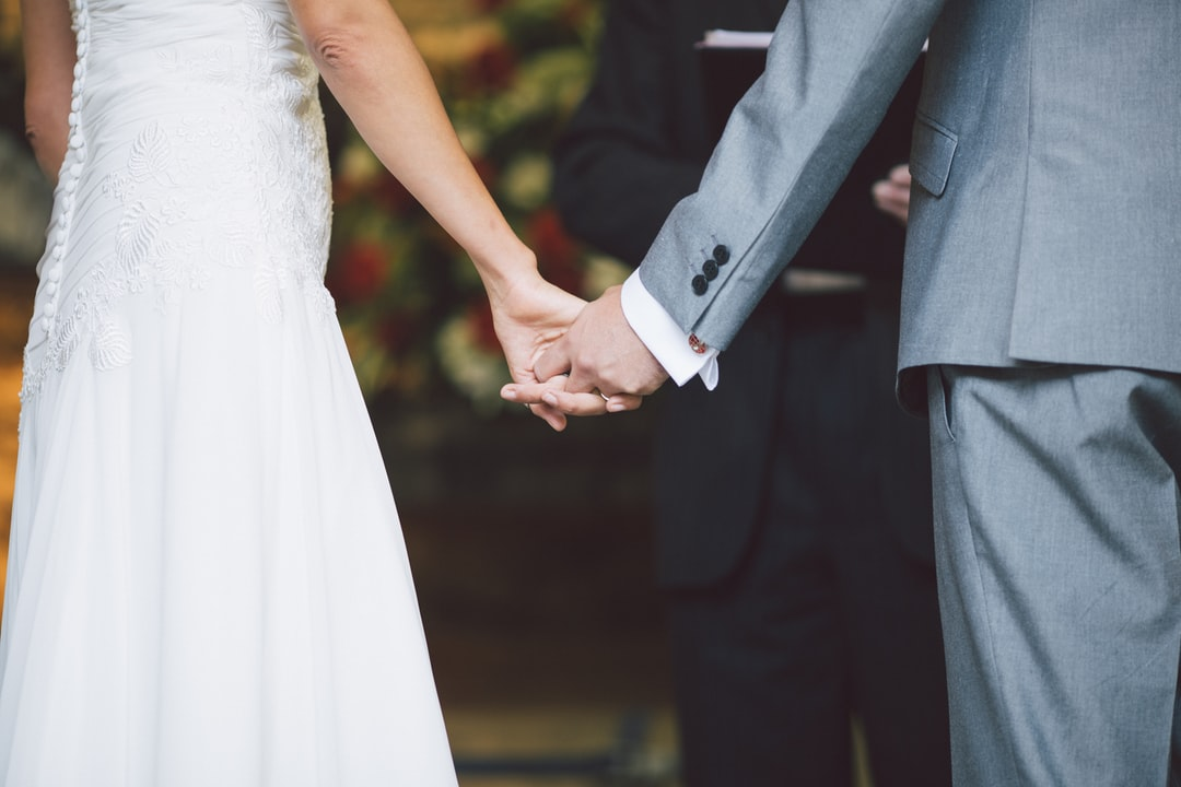 BRIDE AND GROOM HOLDING HANDS IN CEREMONY