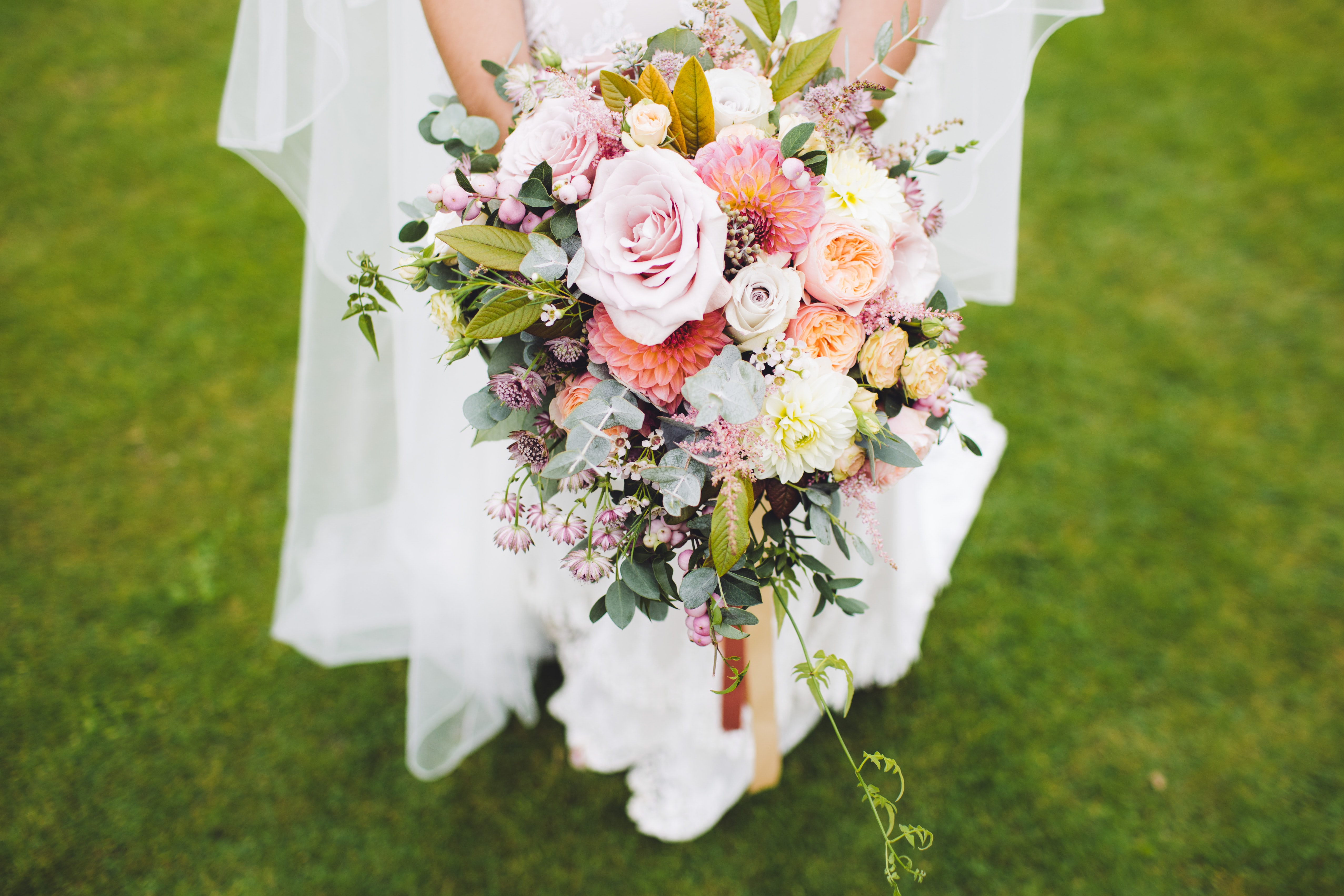 newlywed woman holding bouquet standing on green grass
