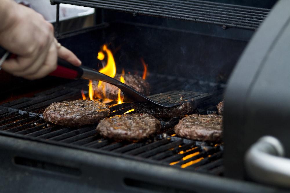 person grilling hamburger patties