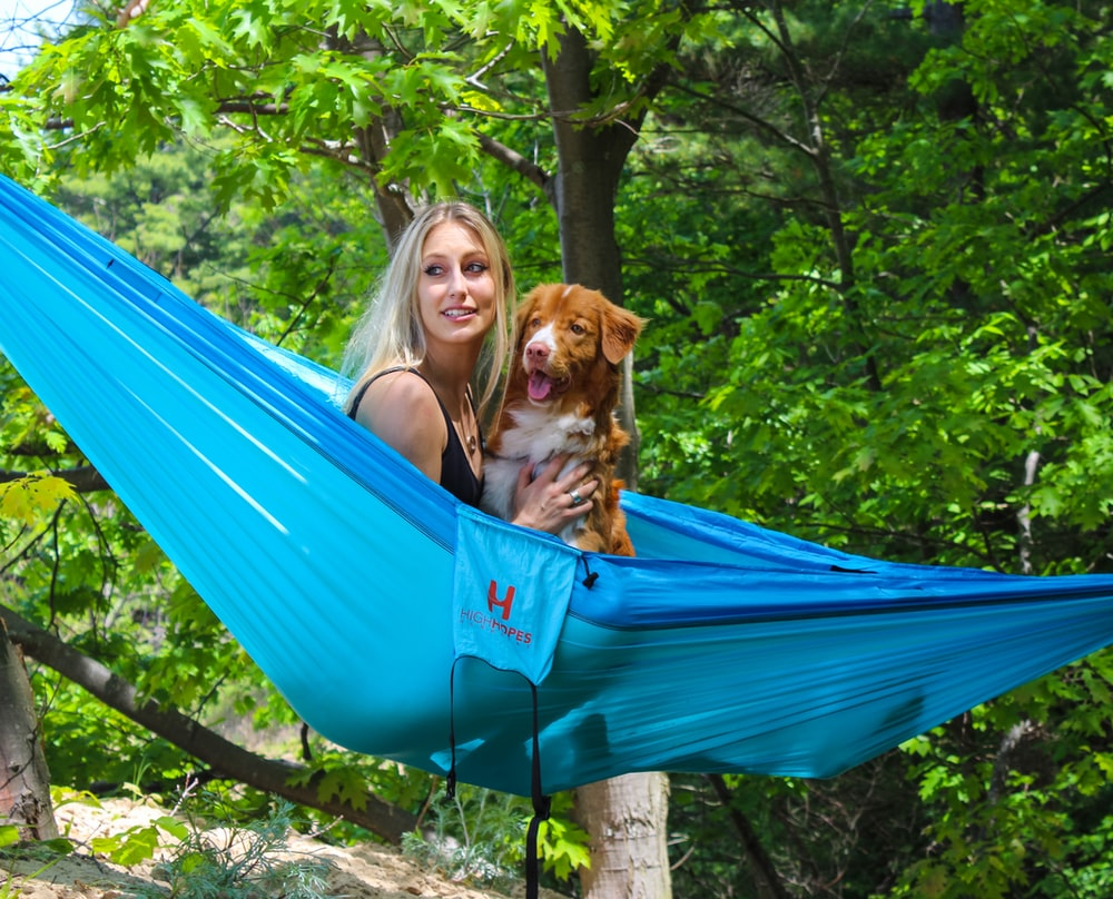woman and dog on blue hammock