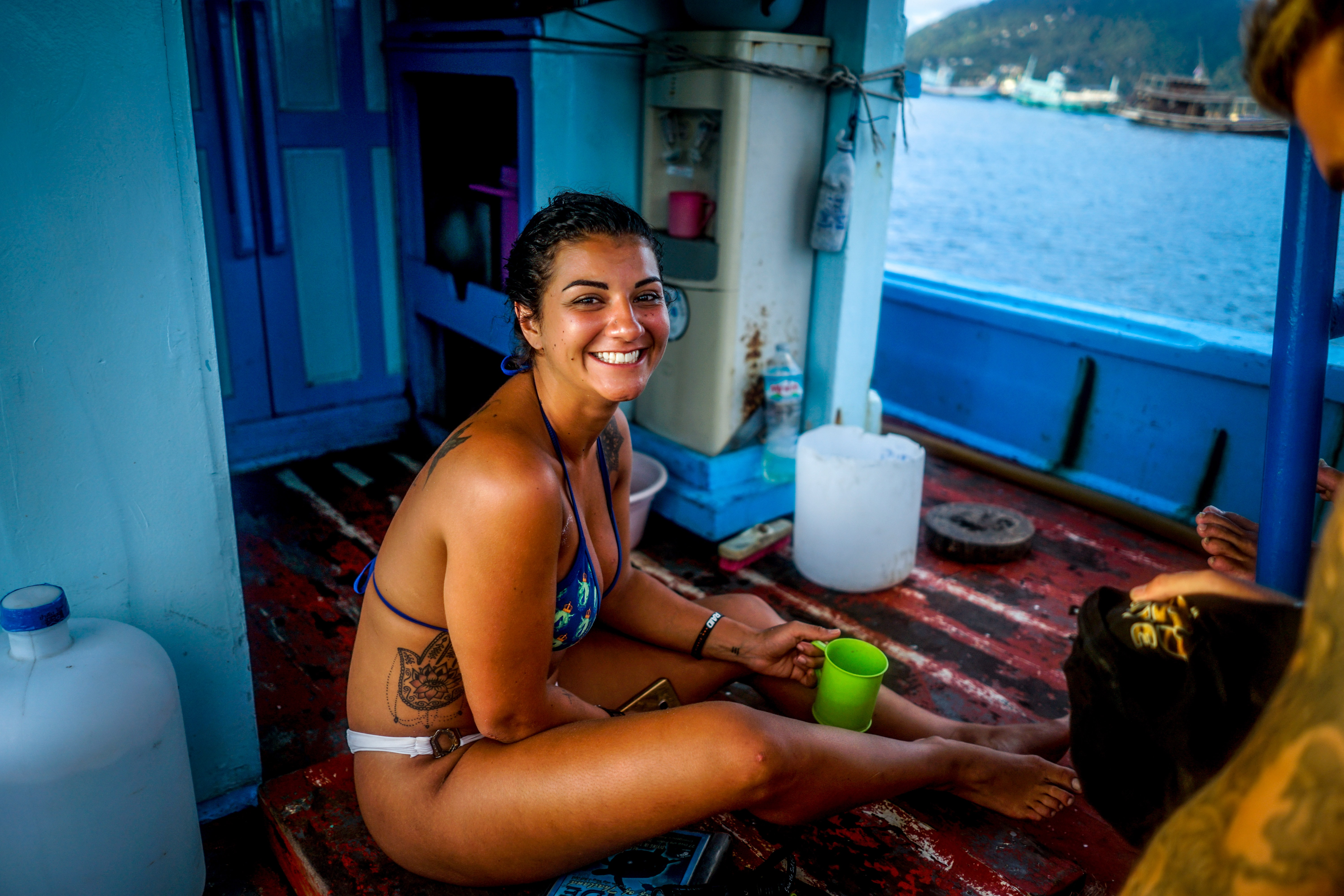 woman in blue bikini top holding green mug while sitting inside boat