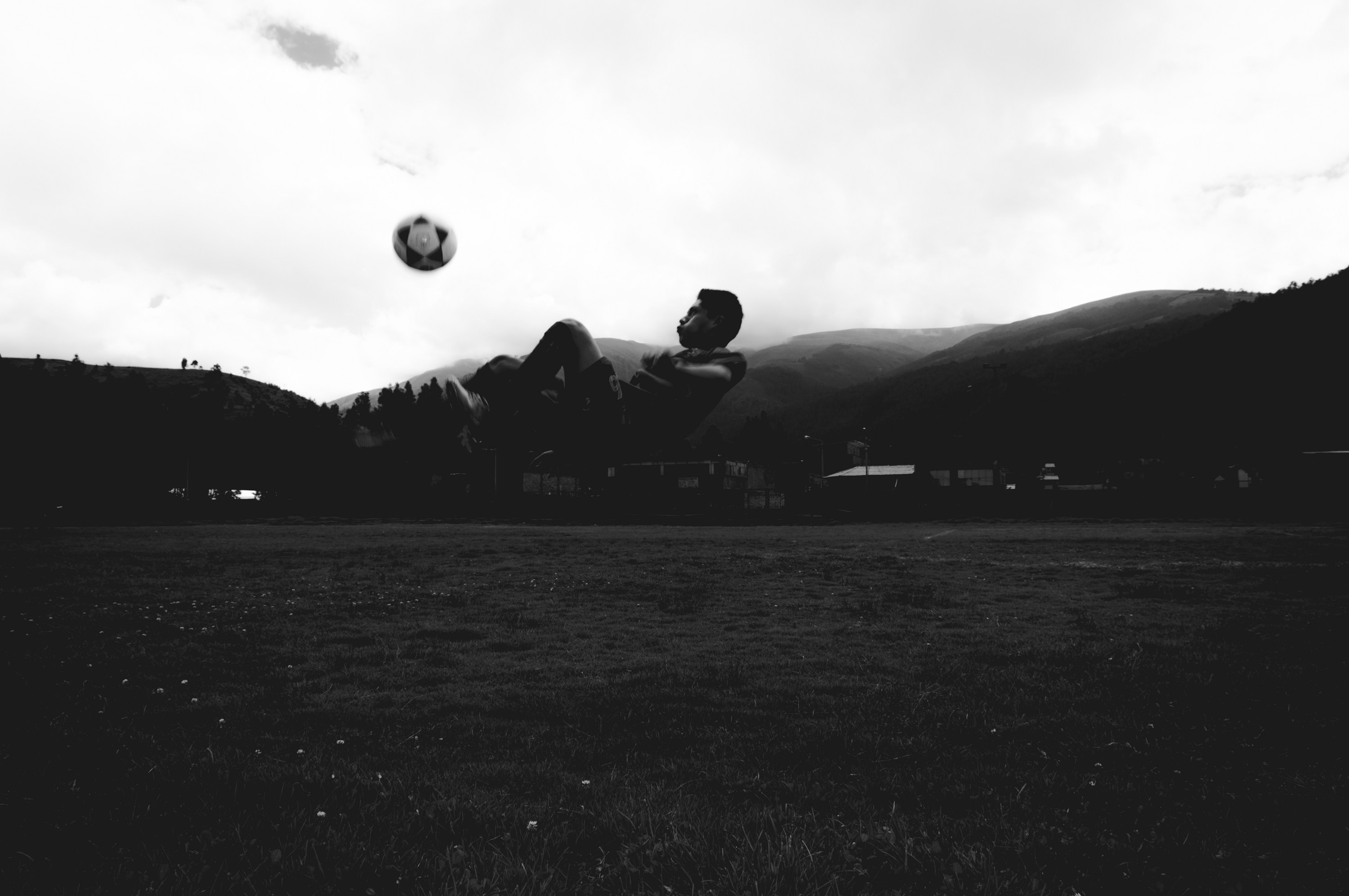 grayscale photo of man playing soccer