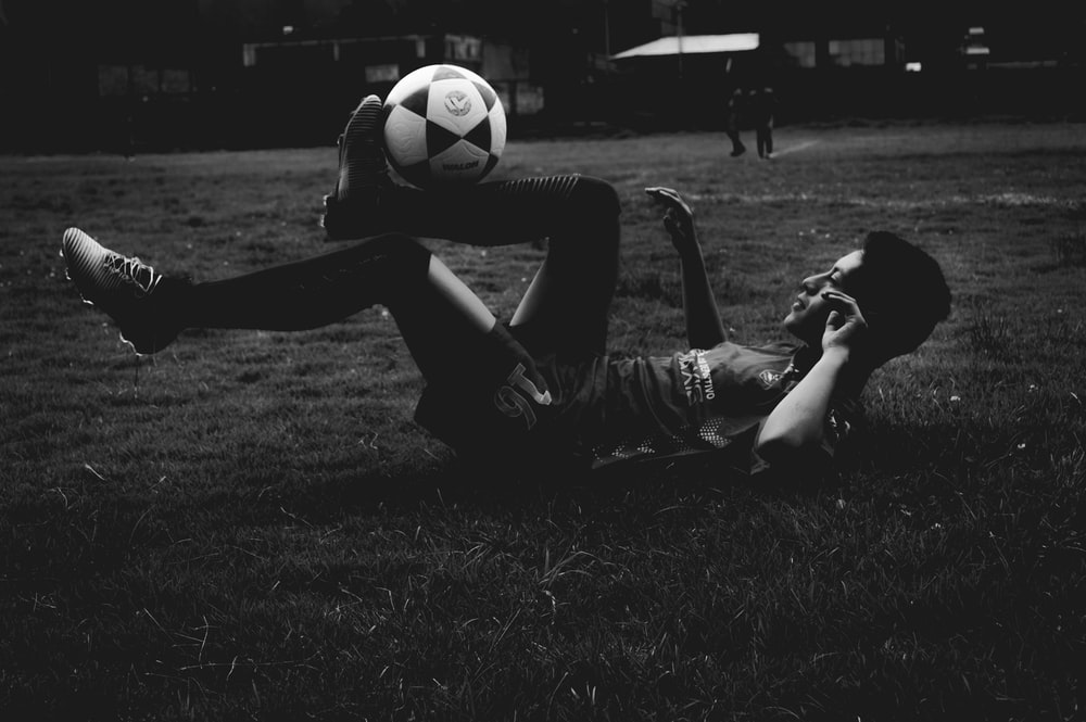 man lying on field while playing soccer ball