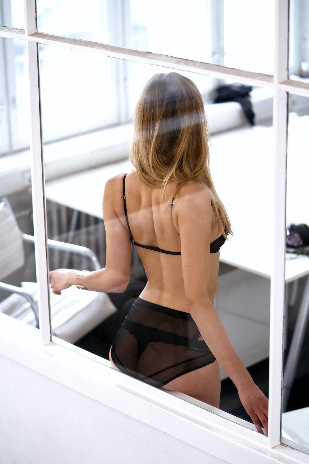 woman wearing bikini leaning beside clear glass window