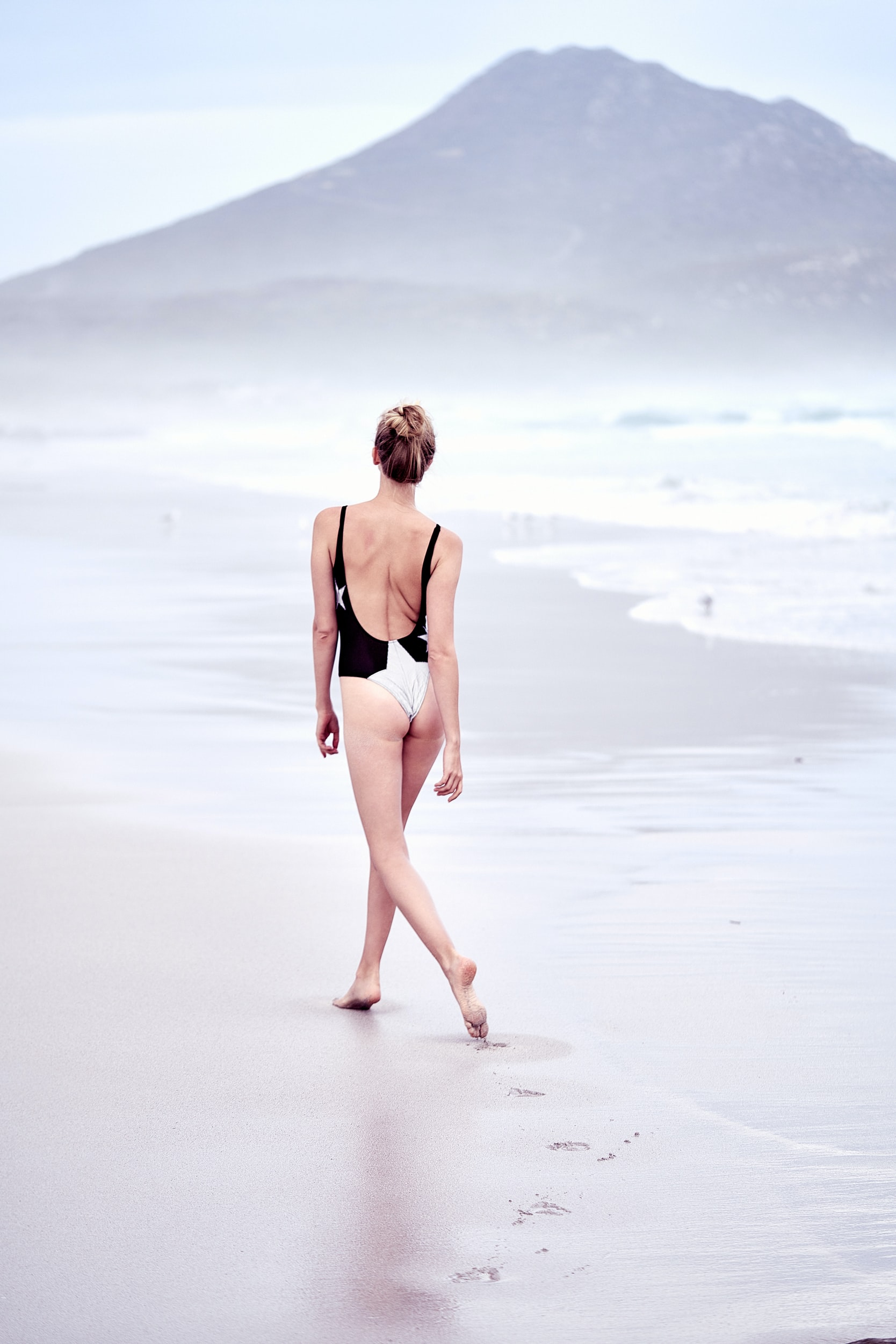woman in one-piece swimsuit walking on seashore