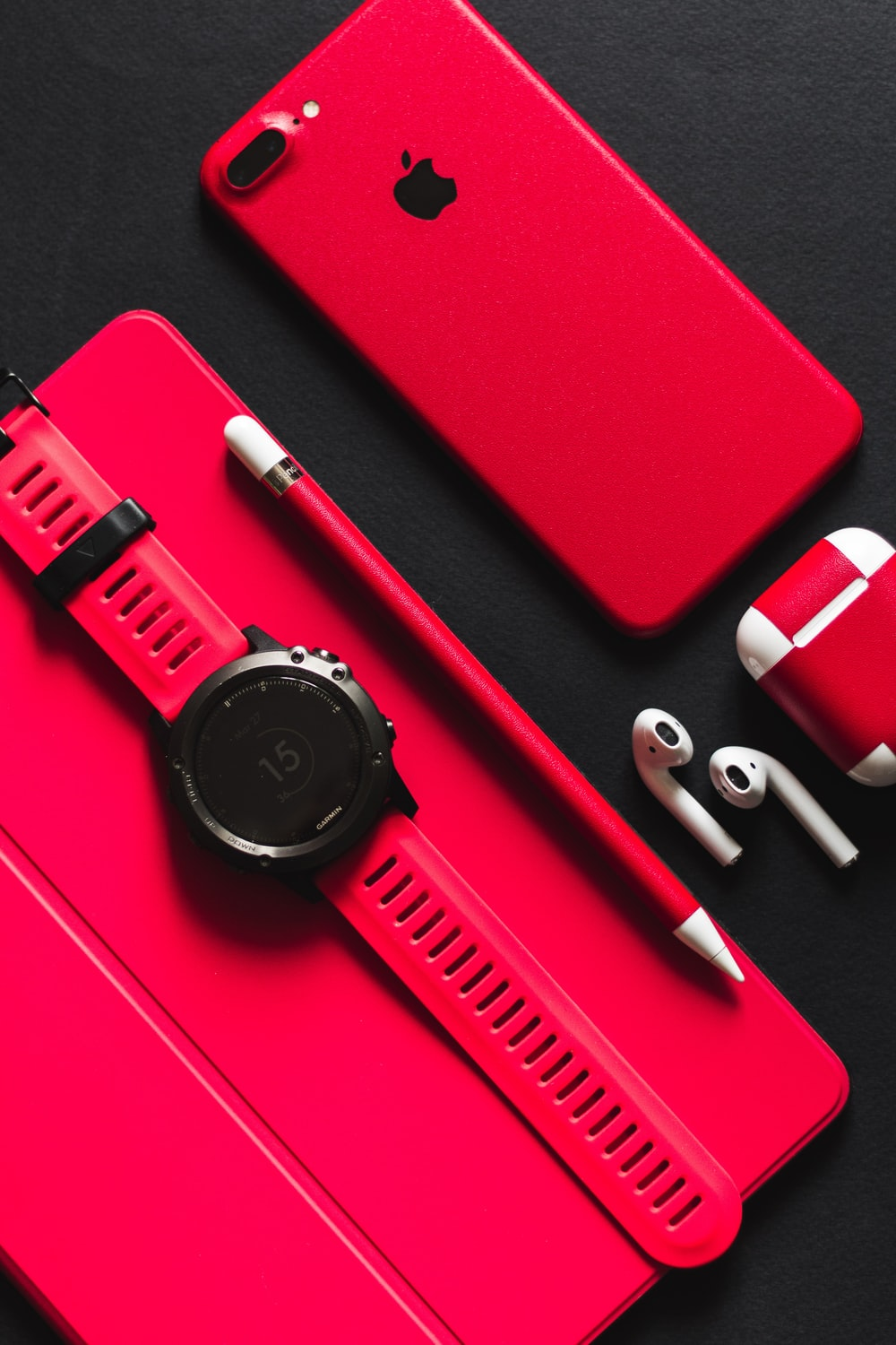 smartwatch, stylus, AirPods, and product red iPhone 7 on black surface