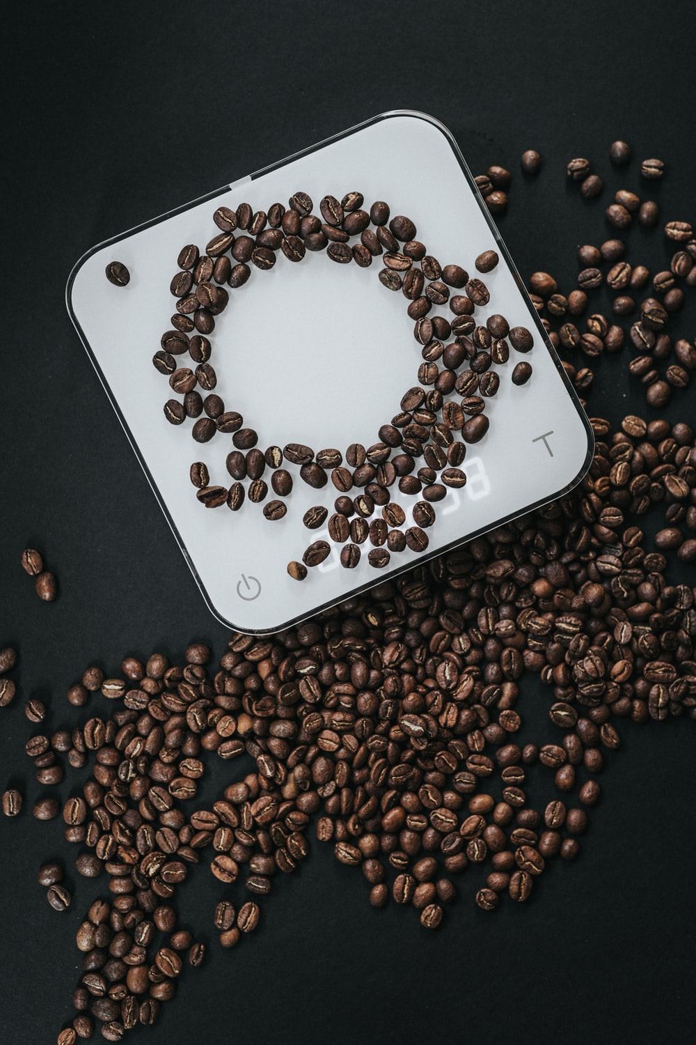 coffee beans on top of white cube scale in closeup photography