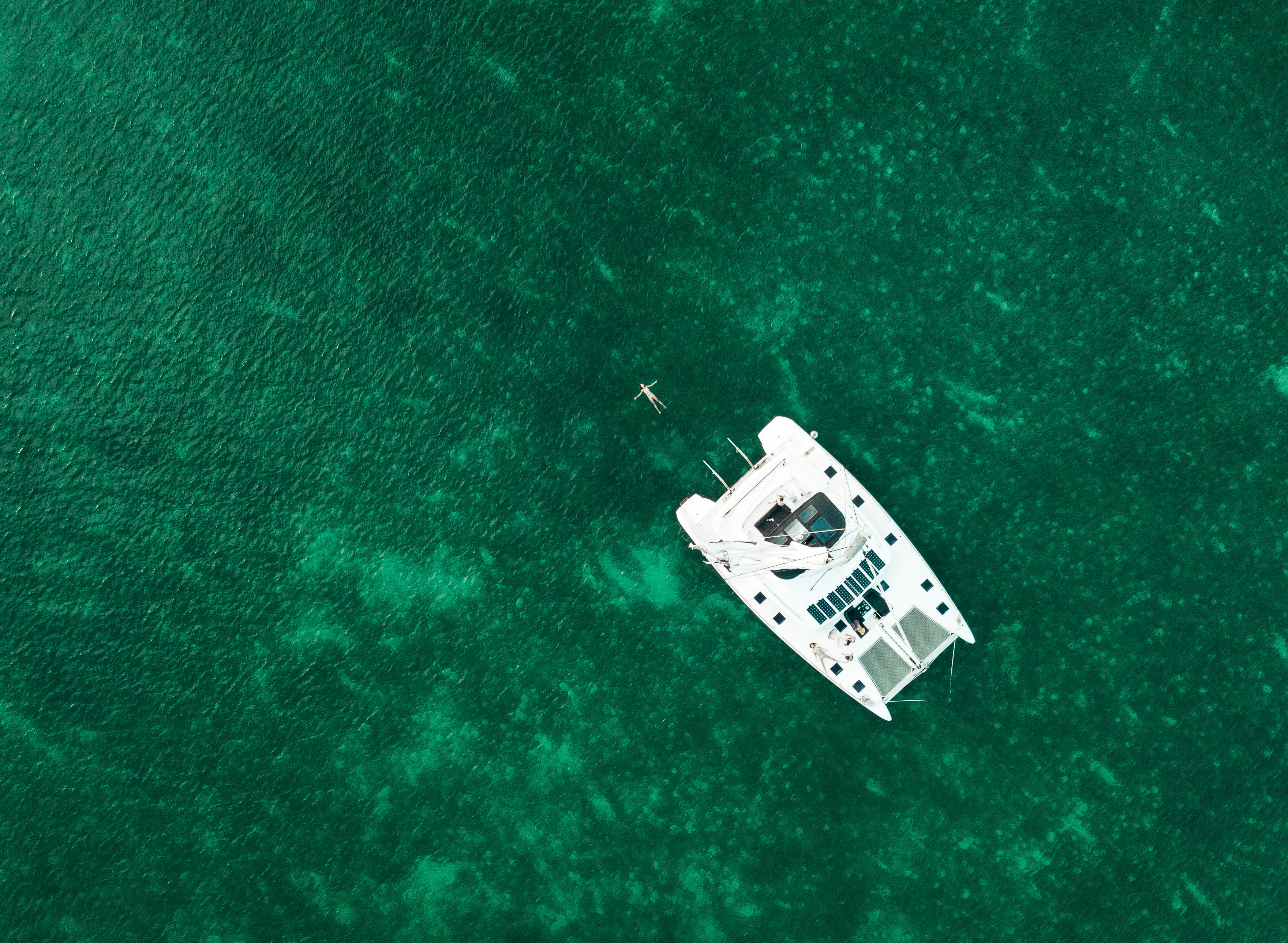 aerial view photography of white boat in the middle of body of water during daytime