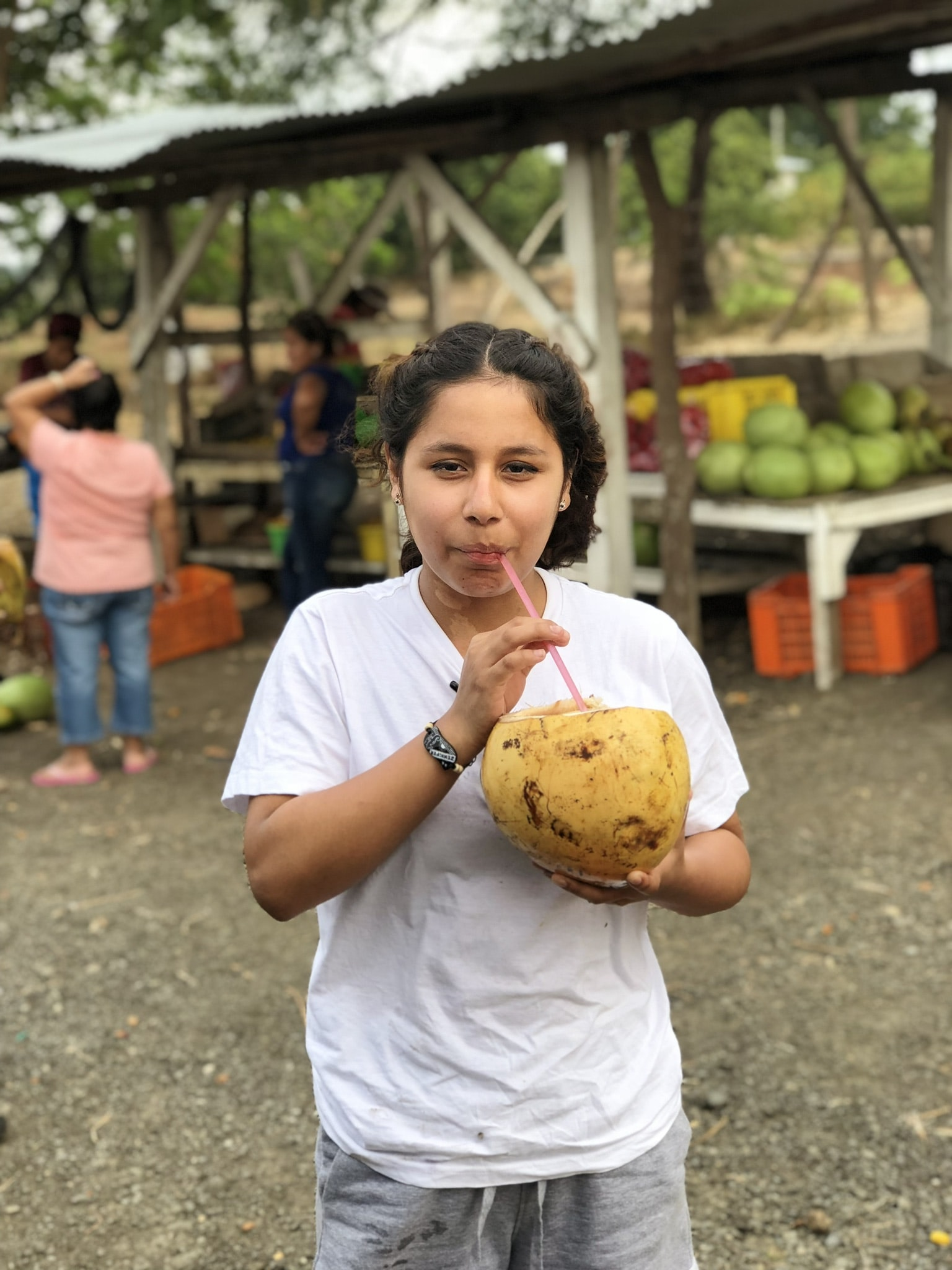 woman sipping coconut fruit