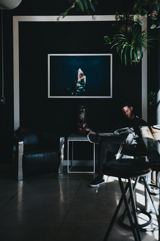 man sitting on chair reading magazine