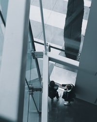 high-angle photo of two person taking to each other