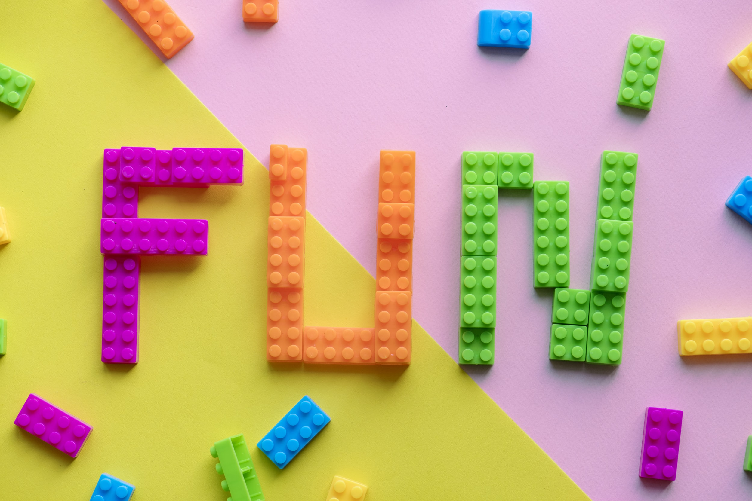 pink orange and green blocks formed into the word fun on flat surface