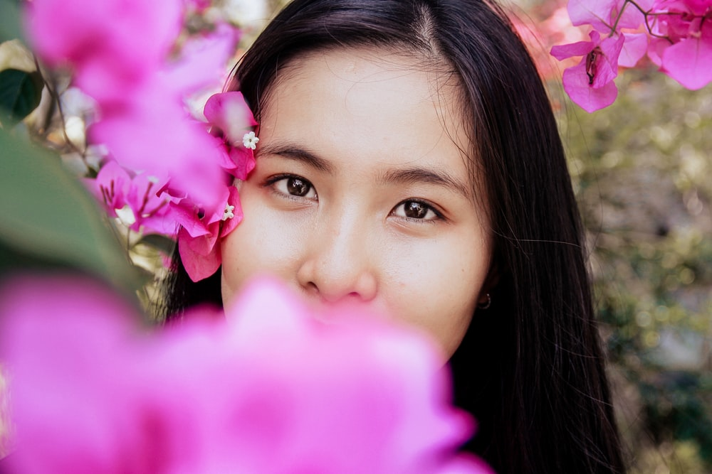 shallow focus photography of woman covered by pink flowers