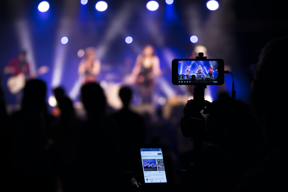 people taking videos during concert