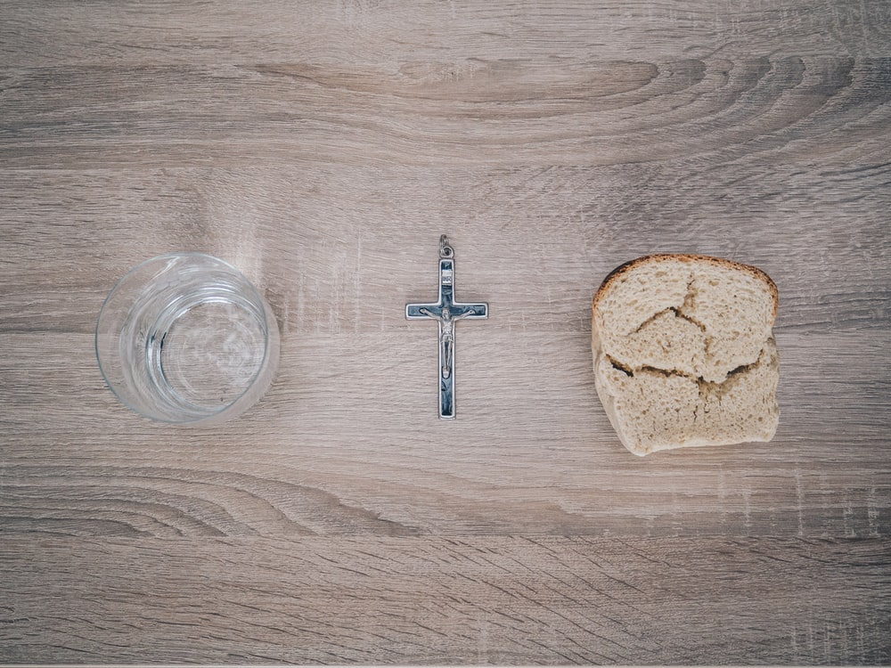 closeup photo of silver-colored cross pendant beside baked bread