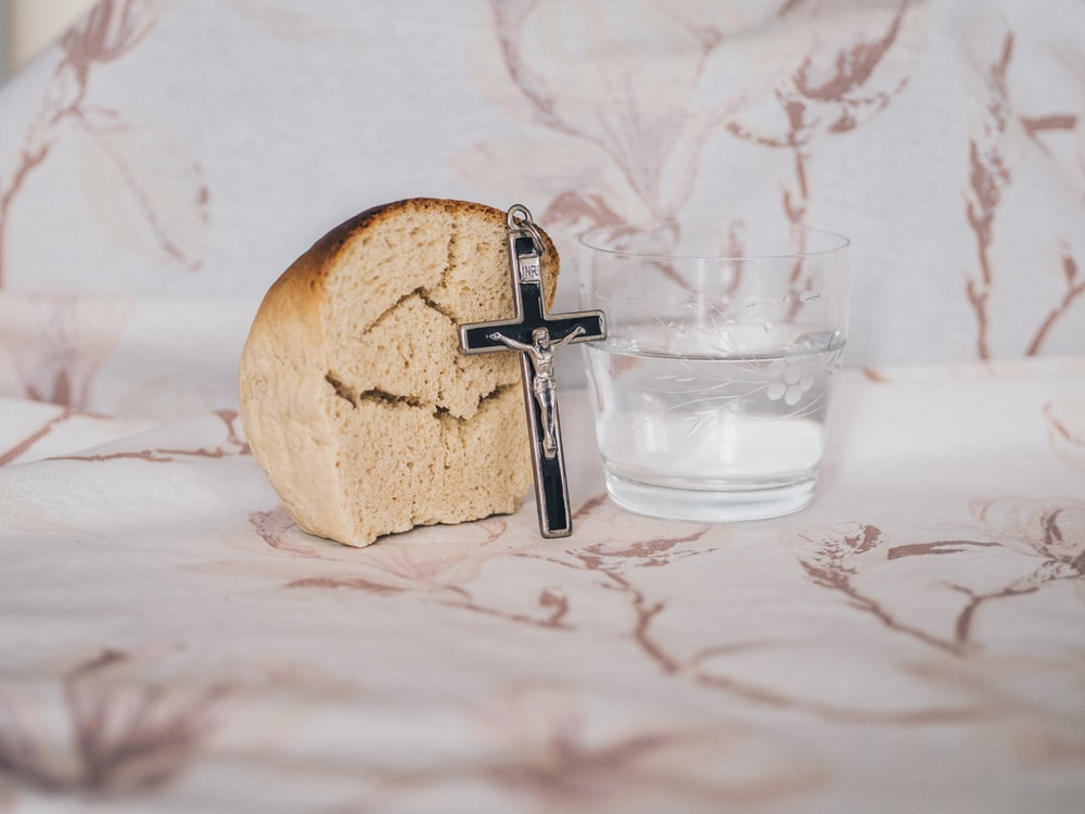 Crucifix pendant on bread beside glass