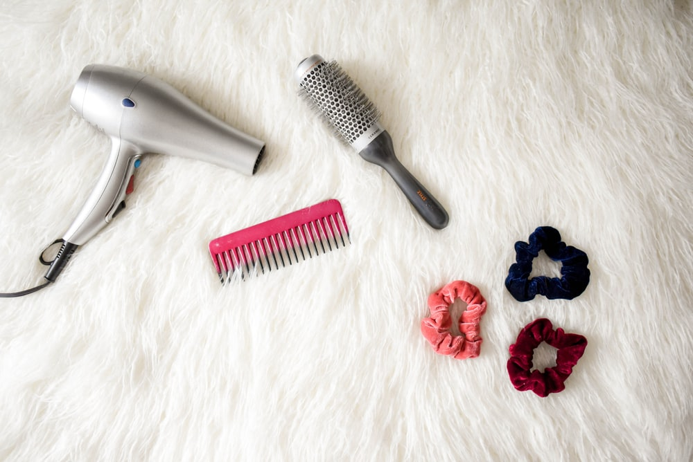 gray corded hair dryer and red comb