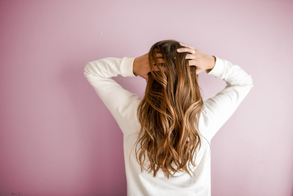 woman in white long-sleeved shirt standing in front of pink wall