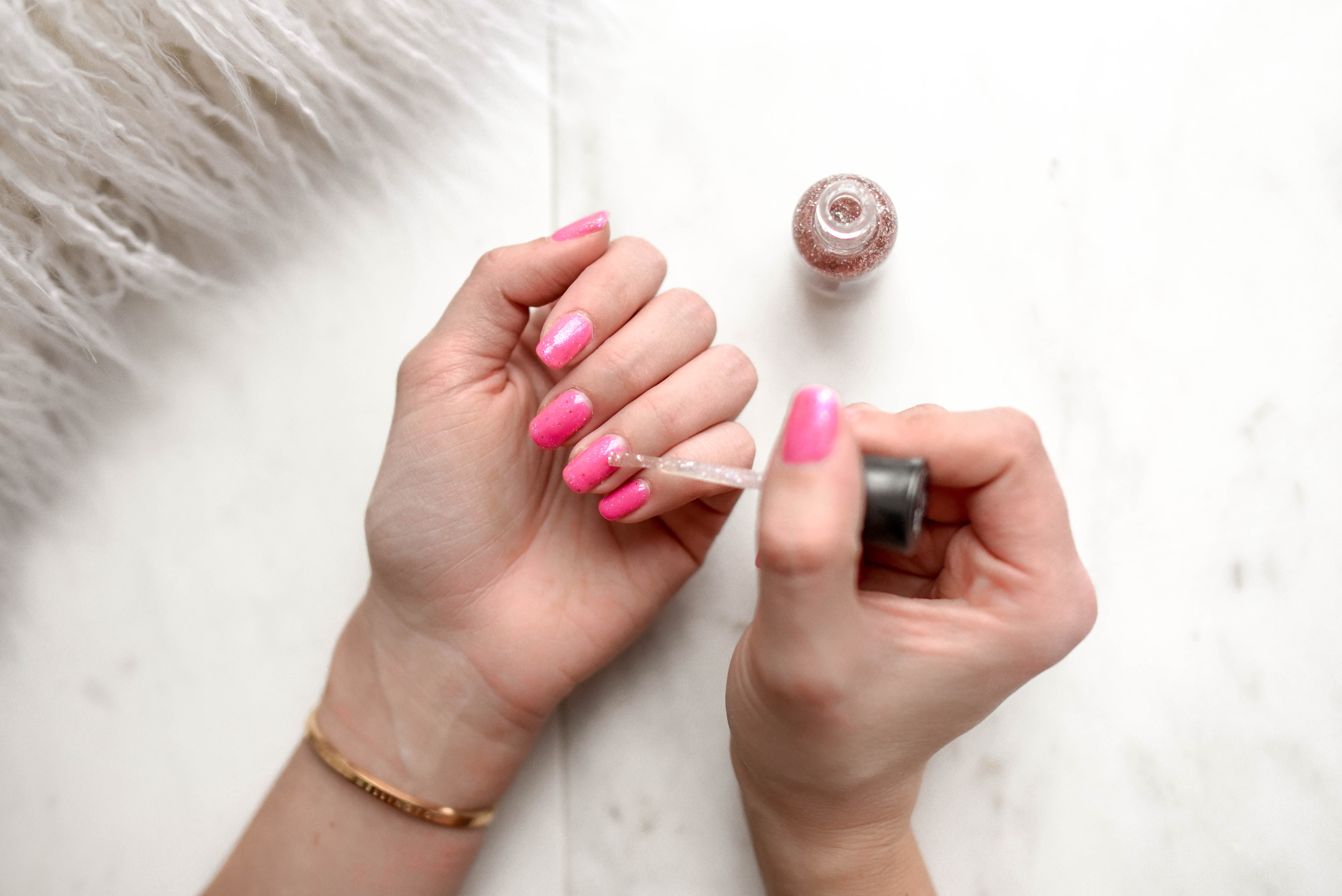 person spreading glittered nail polish on pink nails