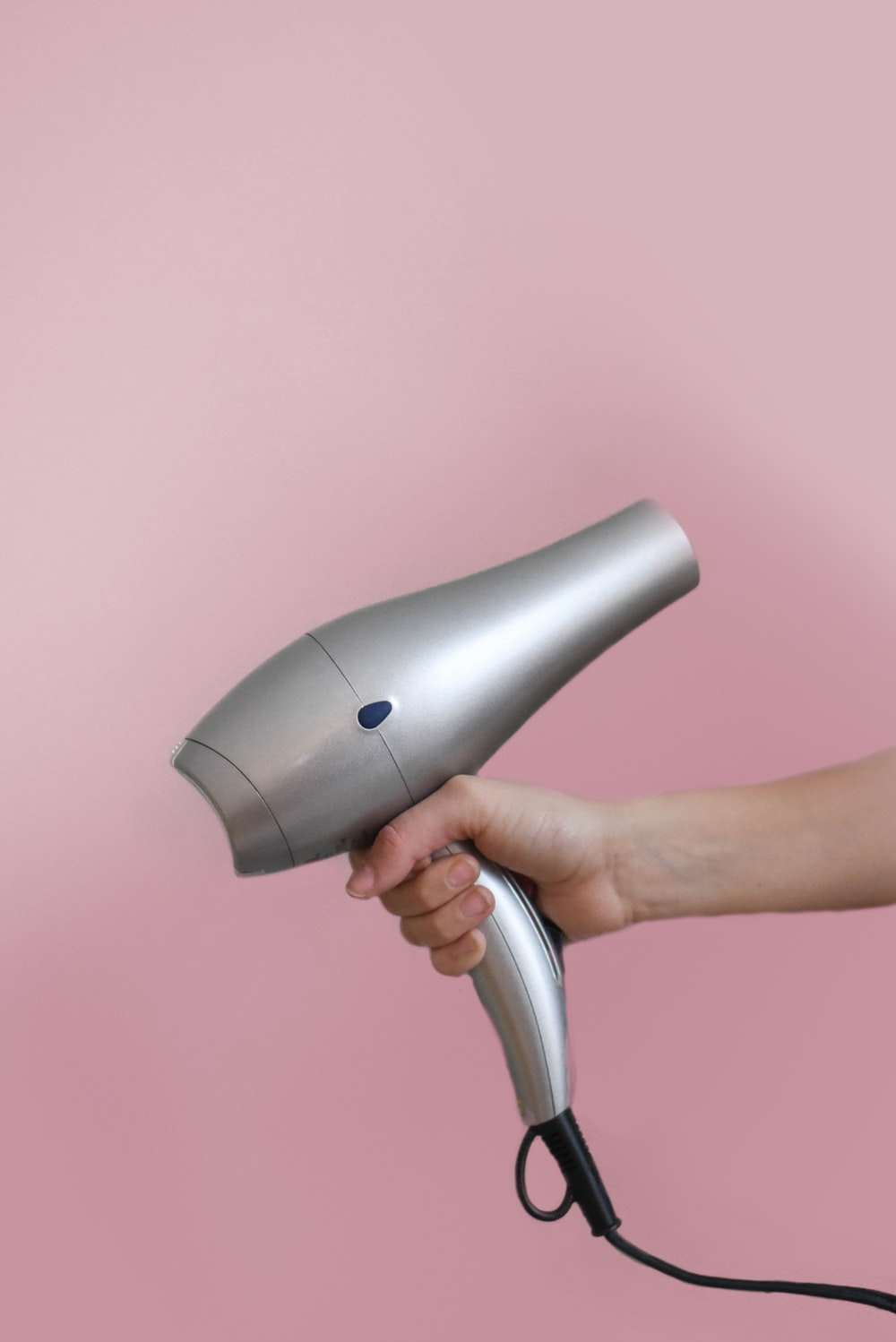 person holding gray corded hair dryer