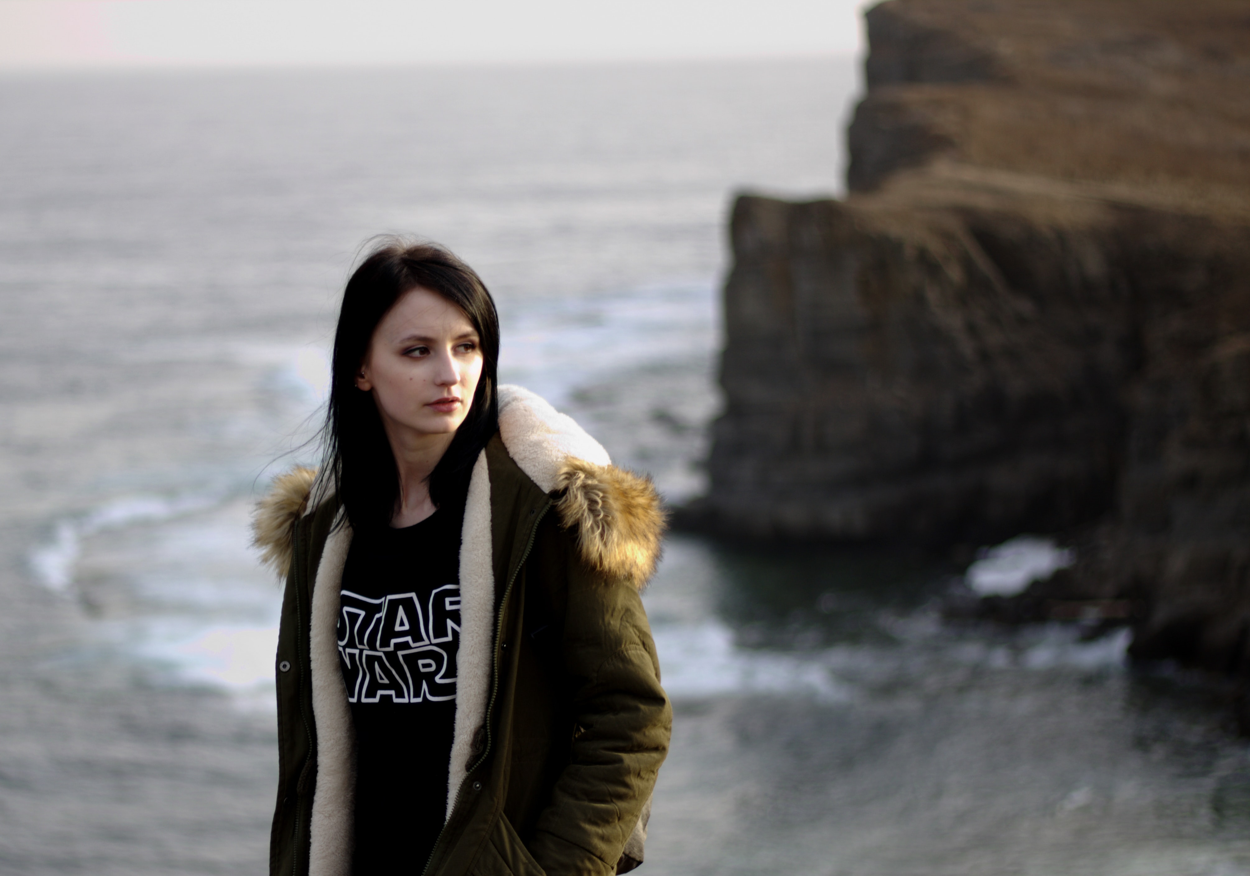woman in brown parka jacket standing on rock formation