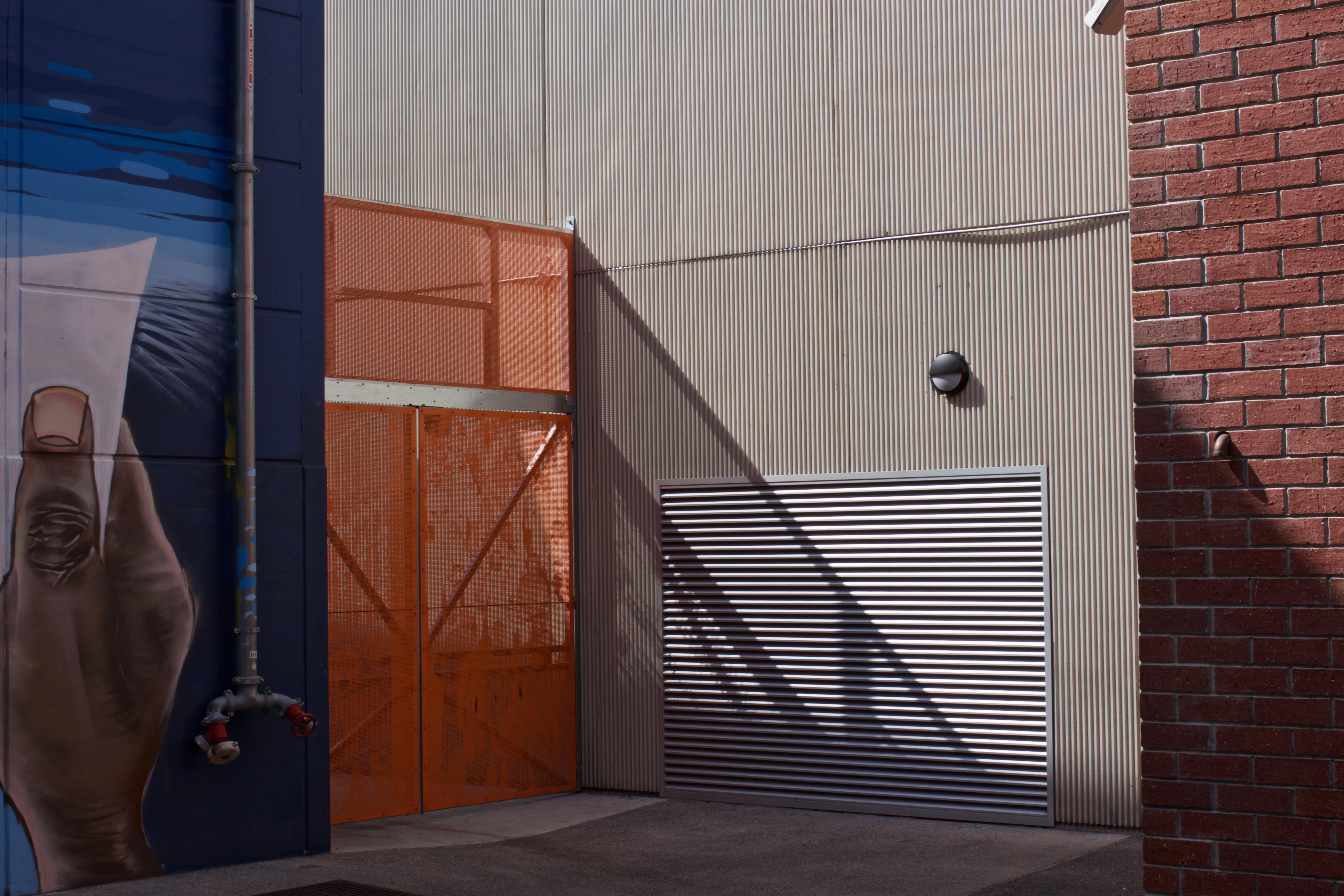 white roller shutter beside orange metal gate