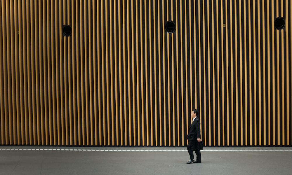 man in black suit jacket walking on road