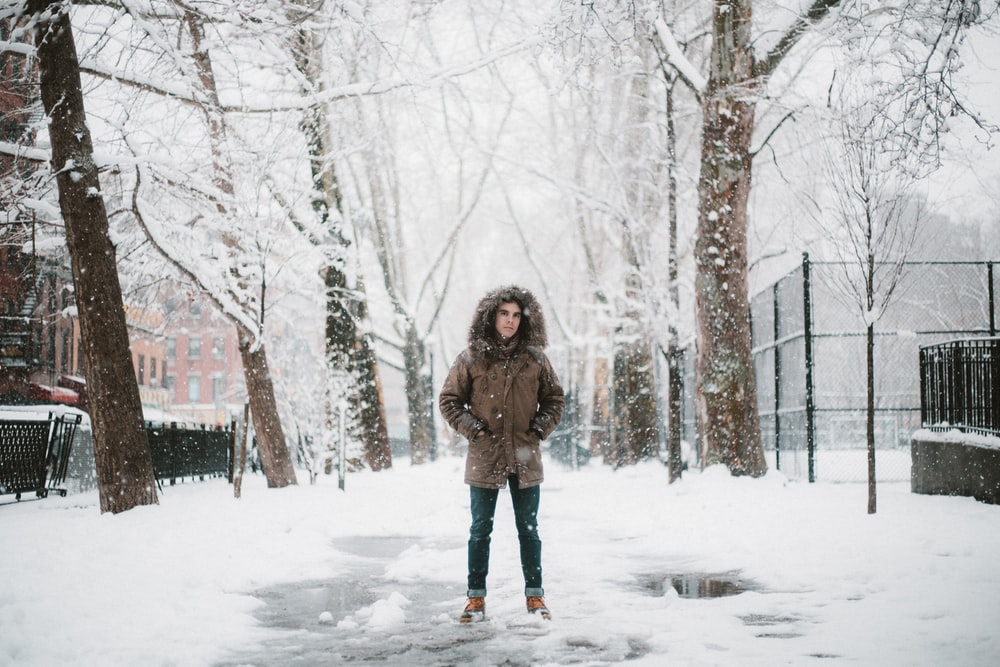 standing person on white snow field during daytime