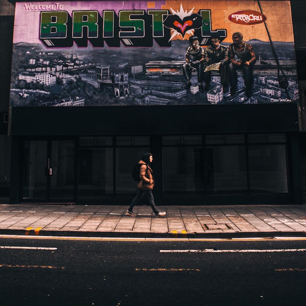 person walking on street beside store