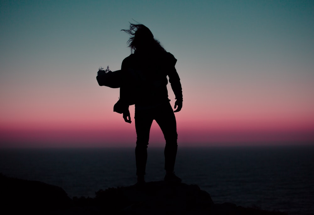 silhoutte of person standing on mountain