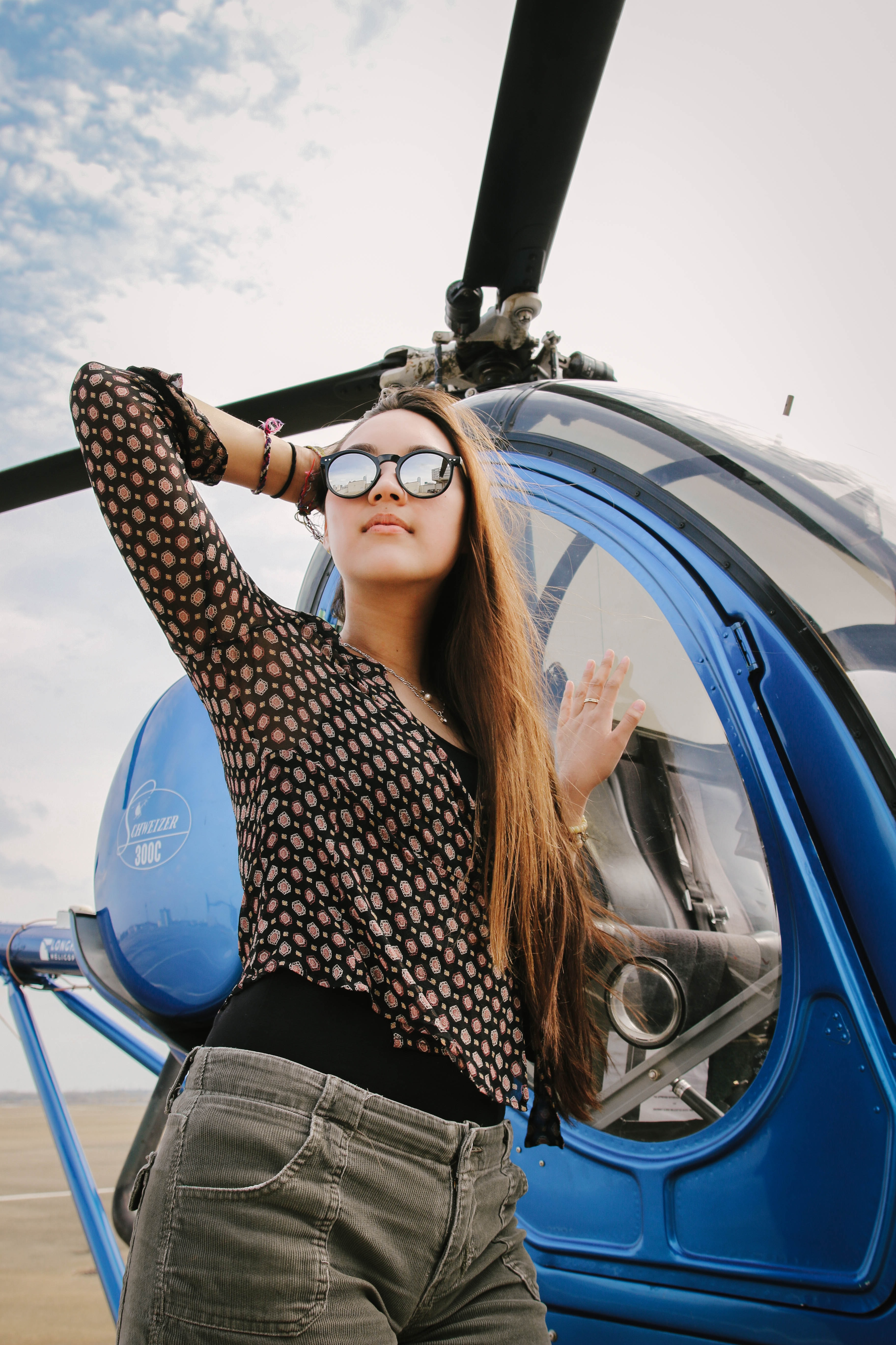 woman standing beside blue helicopter
