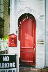 closed red wooden door beside No Parking signage