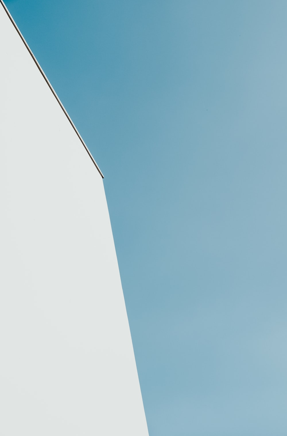 white concrete building under teal sky