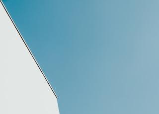 white concrete building under teal sky