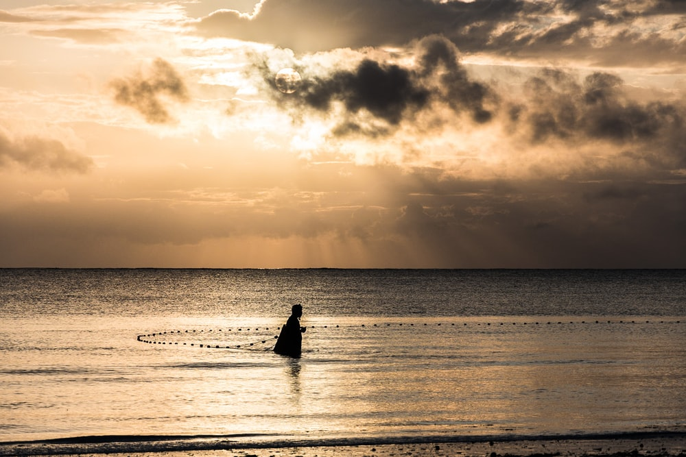 person on ocean during sunrise
