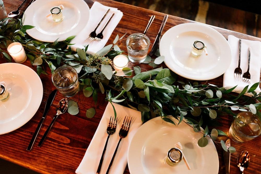 white ceramic dinner plate set on brown wooden table
