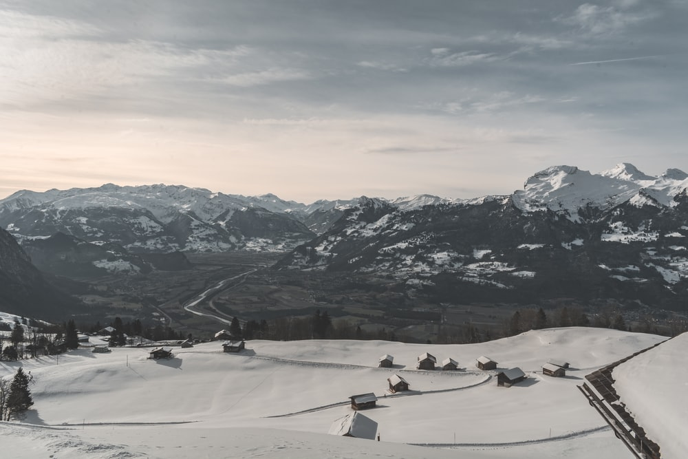 aerial view of village near mountain covered with snow