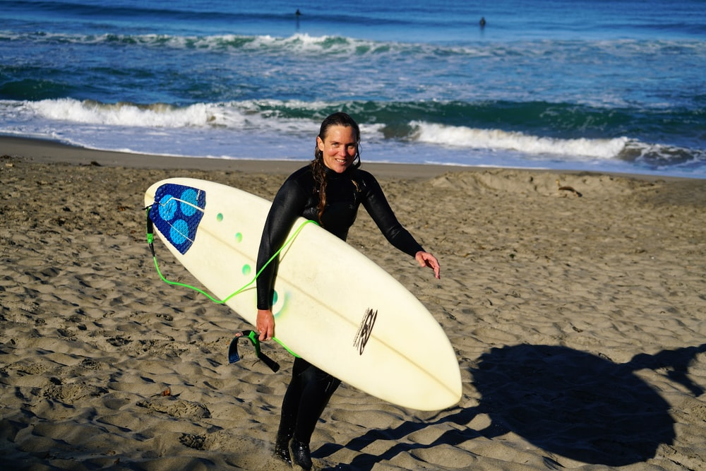 woman holding surfboard standing on sea shore