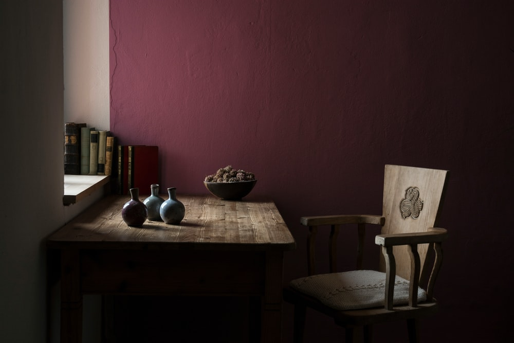 three vases on table beside chair inside maroon painted room