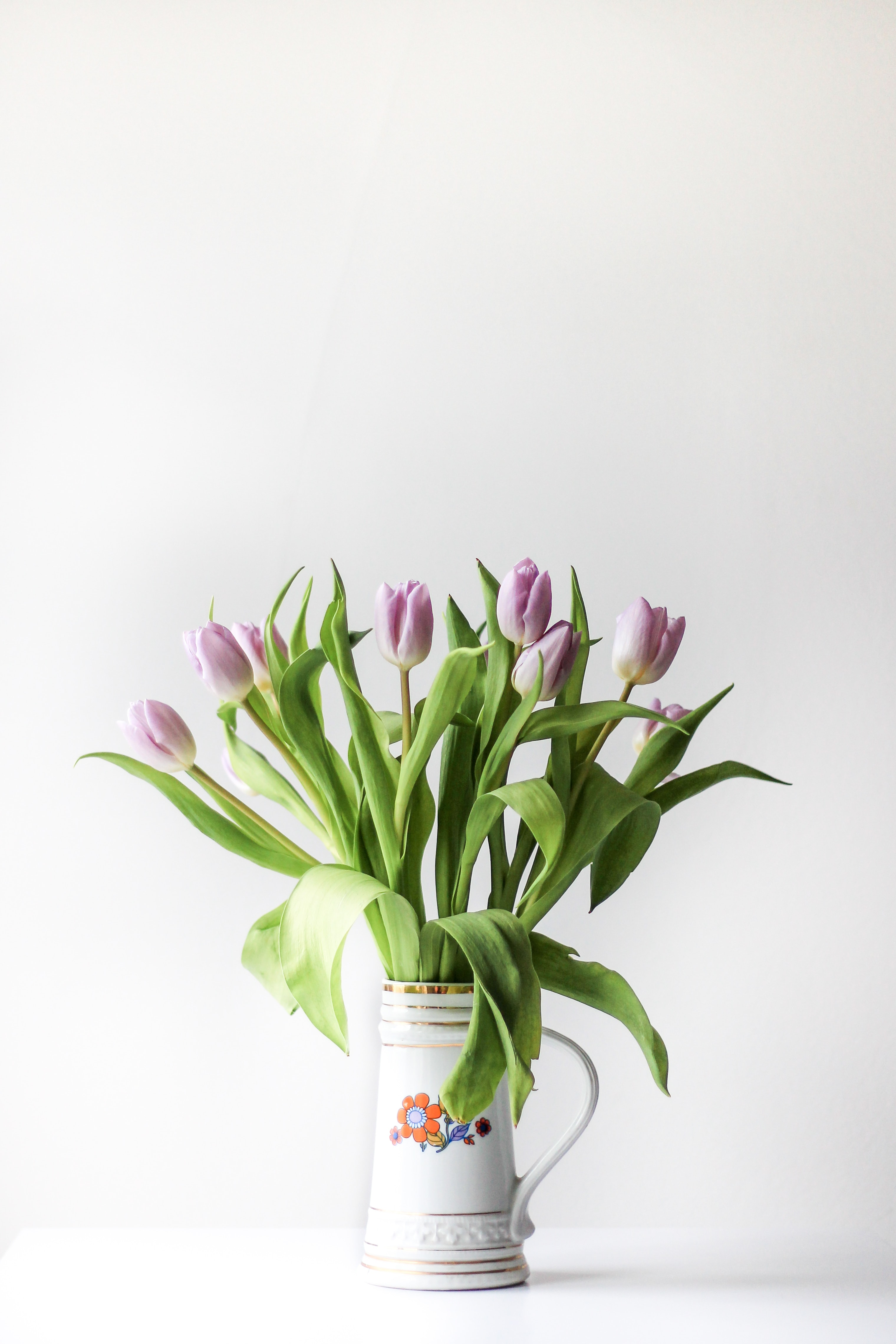 selective focus photography of purple tulip flower arrangement