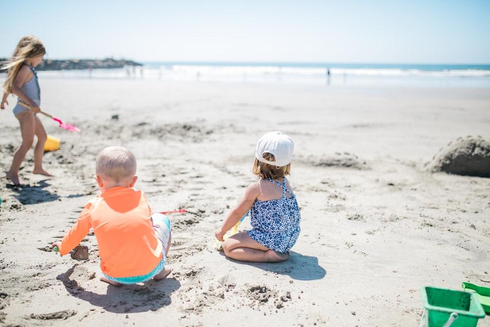 three children playing at the beach
